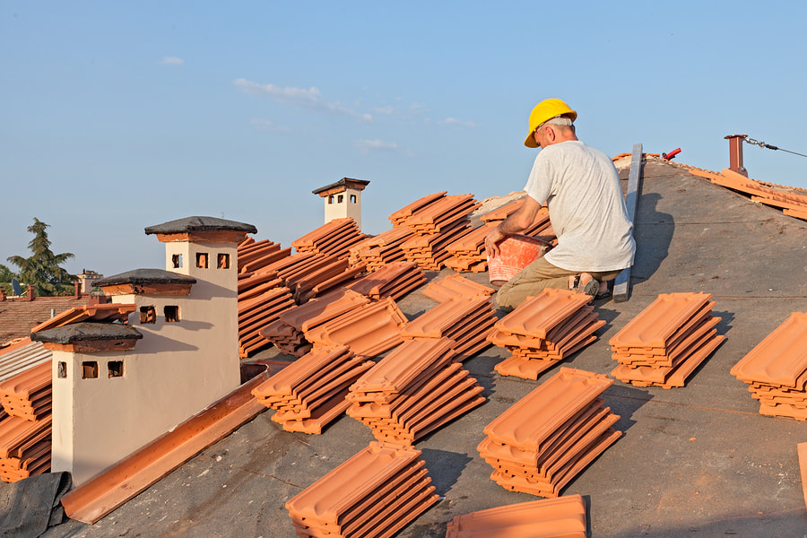 construction worker installing roof shingles
